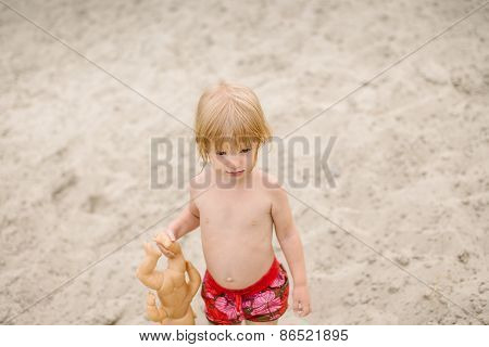 Cute toddler girl at the beach playing with her baby doll