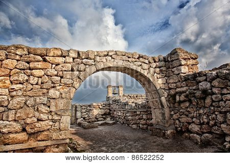 Alarm Ancient Bell Is Visible Through An Ancient Stone Arch On Ruins Of The Ancient Greek City Of Ch
