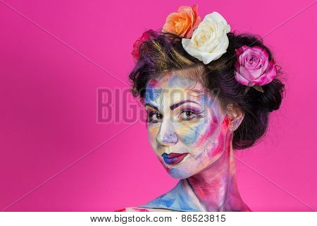 Model with colorful make-up and roses in hair.