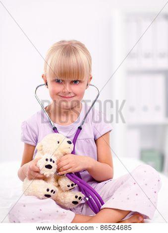 Little girl is examining her teddy bear using stethoscope .