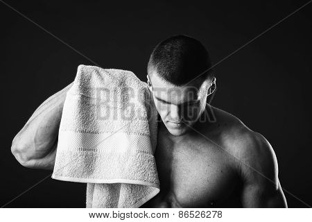 Healthy muscular young man after a workout on dark background.