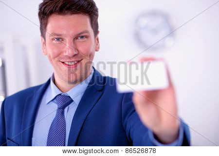 Portrait of young man holding blank white card, isolated