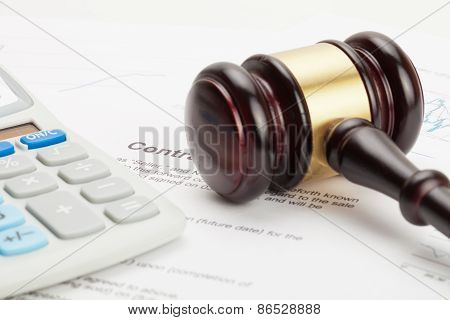 Wooden Judge's Gavel And Calculator Over Some Financial Documents