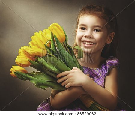 little girl and yellow tulips