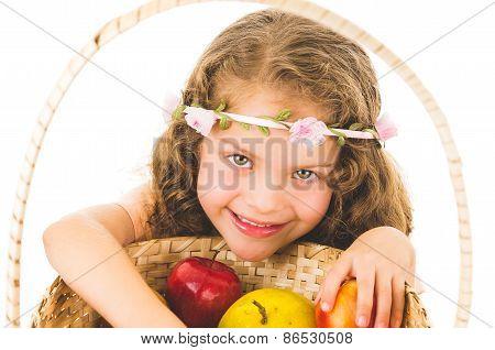 Cute little preschooler girl with fruits on a basket