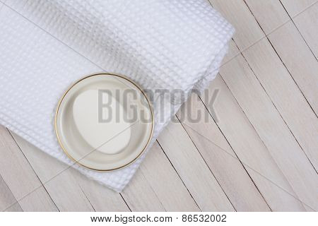 High angle shot of a white bath towel on a whitewashed wood surface. On the towel is a bar of soap in a dish.
