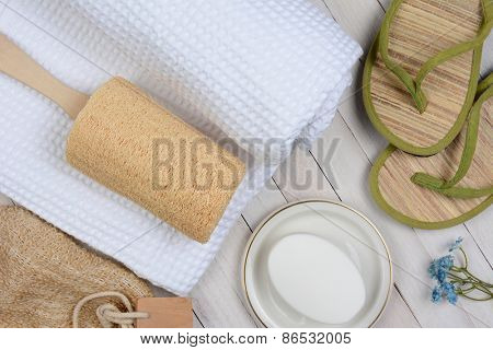 Spa and bath still life. High angle shot of bathroom accessories including, towel, soap, loofah and sandals, on a rustic white wood surface.