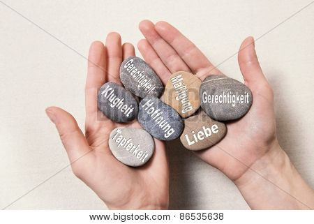 Inner balance concept: hands holding stones with german words for: hope, courage, intelligenz, justice, equality, love and temperance,