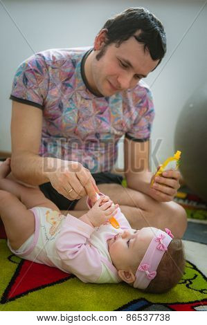 Papa feeds child with spoon. Image of young dad