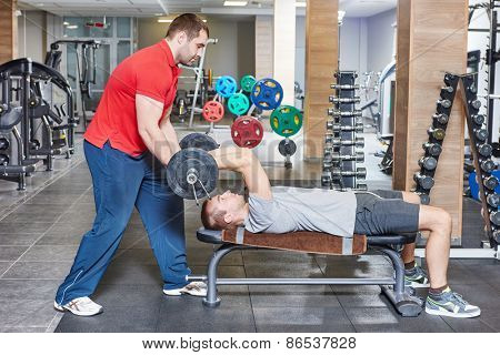 fitness and sport concept. personal coach trainer helps man work out at a gym with heavy weight