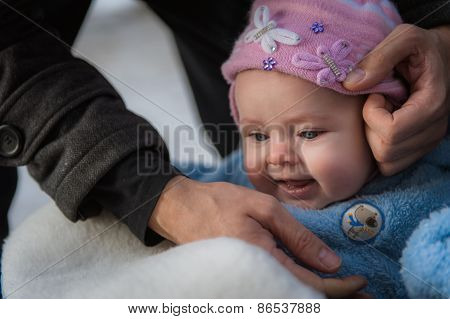 Smiling baby sitting in sledge. Happy infant girl while Hiking