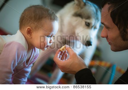 Image of young dad feeds cute little daughter with hands