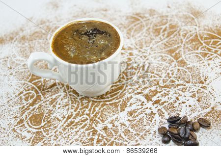 Cup Of Coffee On A Table Covered With Coffee Grains