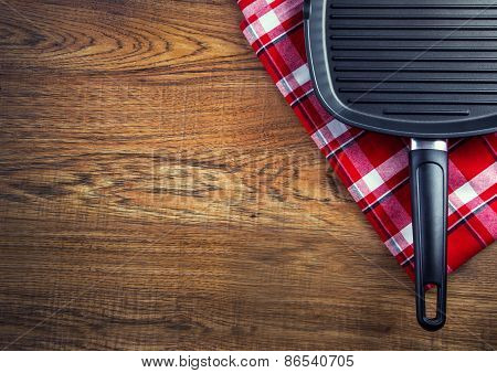 Top view of checkered napkin and teflon pan on wooden table. Free space for your informatio