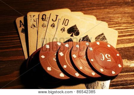 Playing cards with chips on wooden table, closeup