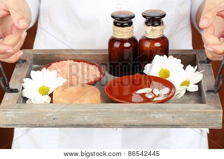 Beauty therapist holding tray of spa treatments, close-up, on wooden wall background