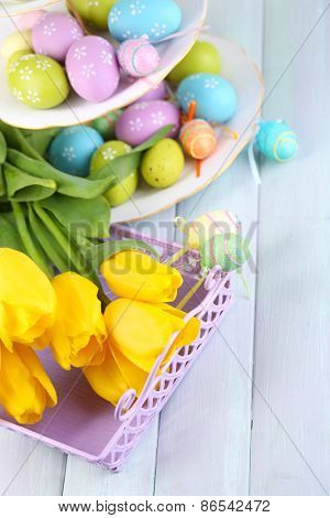 Easter eggs on vase and tulips on table close-up