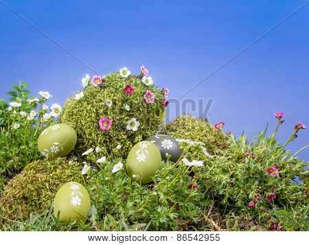 Easter eggs scattered in the grass and giant moss-grown egg with fresh spring flowers over blue sky