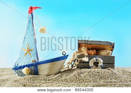Marine still life with toy model of ship on sand on blue background