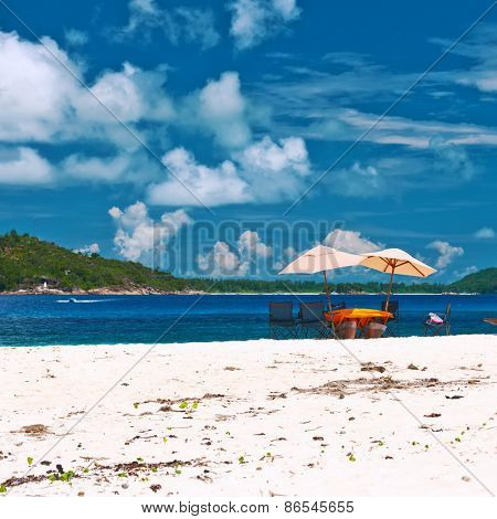 Tropical beach at Seychelles with picnic table and chairs