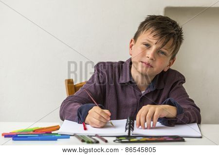 School boy doing homework at his desk.