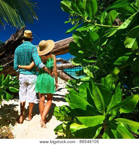 Couple walking to the beach Anse Source d'Argent among tropical foliage at Seychelles, La Digue.