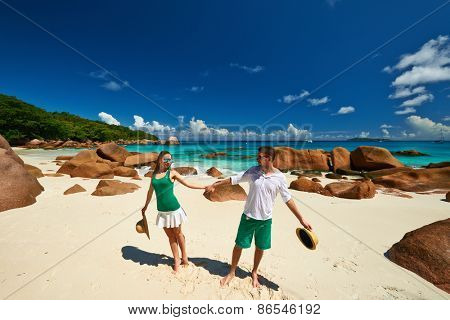 Couple in green having fun on a tropical beach at Seychelles