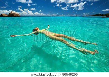 Woman in yellow bikini lying on water at tropical beach