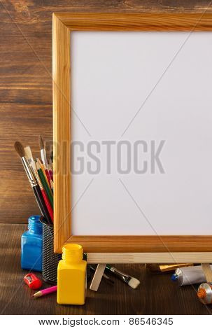 picture frame and paints on wooden background