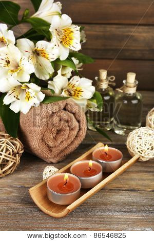 Beautiful spa composition with candles and flowers on wooden background