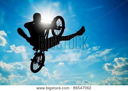Man jumping on bmx bike performing a trick against sunny sky. Extreme sport