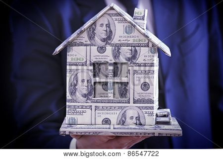 Model of house made of money in male hand, close up