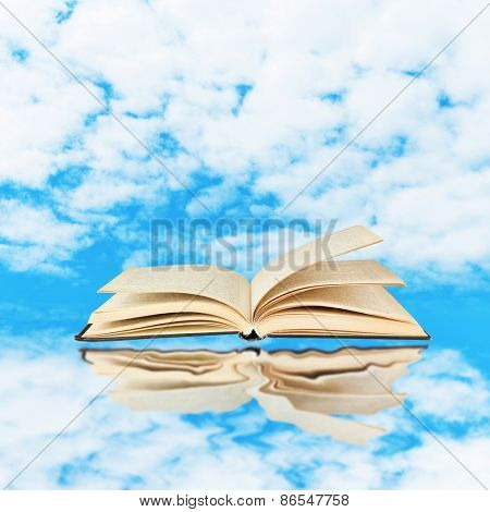 Opened book on sky background