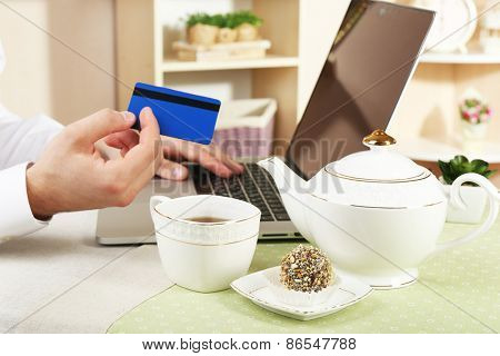 Man holding credit card and working on laptop on home interior background