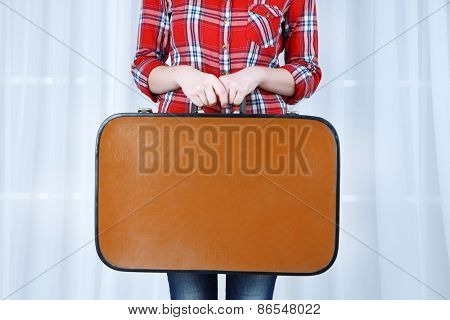 Woman holding old suitcase on fabric background