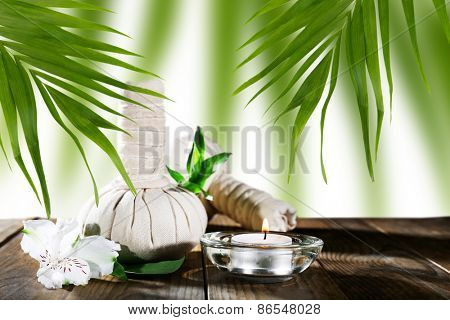 Spa compress balls with green leaves on wooden table