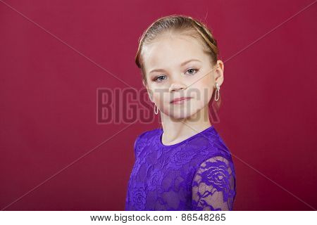 Portrait of beautiful blonde little girl, studio on dark red background
