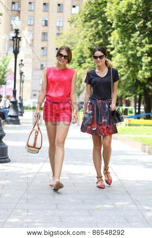 Two young happy women walking in the summer city