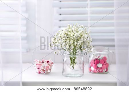 Sweet candies in jar with flowers on windowsill background