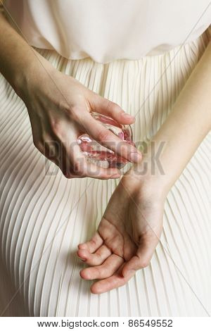 Woman spraying perfume on her wrist, closeup