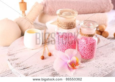 Glass bottles with color spa sea salt on wooden table, closeup