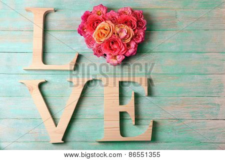 Beautiful roses with word LOVE on color wooden planks background