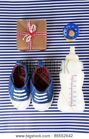 Baby shoes with gift and bottle of milk on blue background