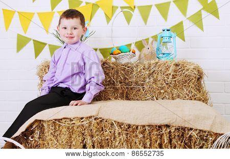 Boy Sitting On A Haystack