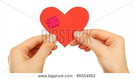 Female hands holding broken heart with patch isolated on white