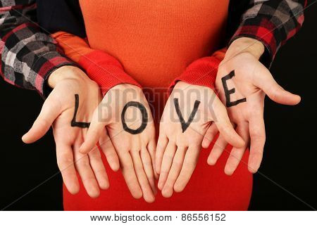 Hands of couple with inscription Love, close-up