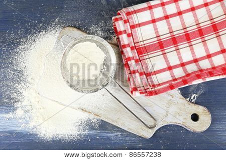 Sifting flour through sieve on cutting board and on wooden table, top view