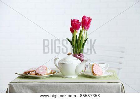 Tea set with flowers on table, on light background