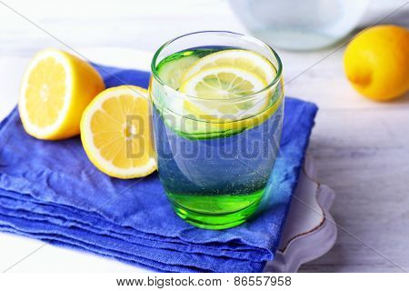 Fresh water with lemon and cucumber in glassware on wooden table, closeup