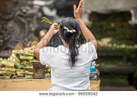 Balinese woman praying, worship front of statue of God